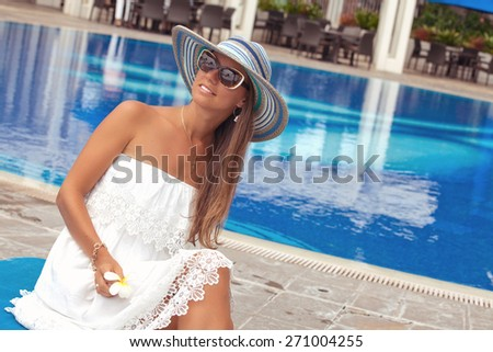 Sexy cheerful woman in summer white dress, relaxing at the luxury poolside. Girl at travel spa resort pool. Summer luxury vacation.  - stock photo