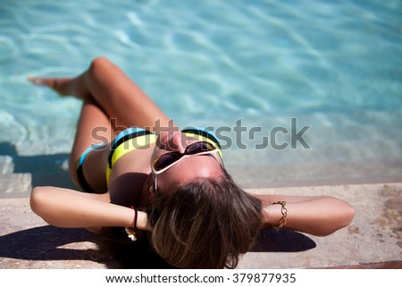 Sexy cheerful woman relaxing at the poolside. Girl at travel spa resort pool. Summer luxury vacation. - stock photo