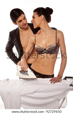 Sexy Couple Doing Ironing. Young man touching the shoulder of a beautiful woman in lingerie who is ironing his shirt, studio on white - stock photo