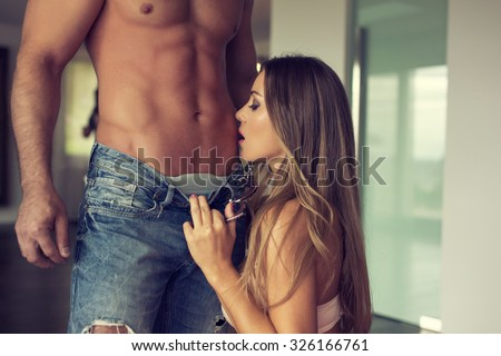 Sexy couple foreplay at home, woman pull down mans jeans, muscular body with abs - stock photo
