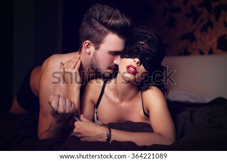 Sexy couple foreplay at night, woman with lace eye cover, sensuality, bdsm
