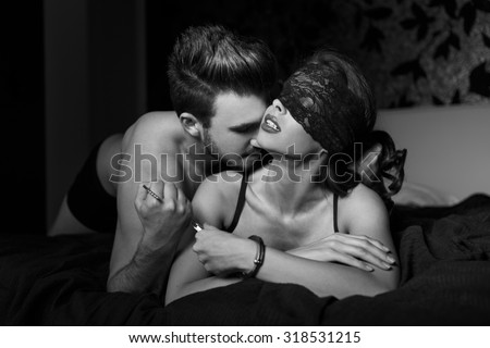 Sexy couple foreplay in bedroom at night, black and white, bdsm - stock photo