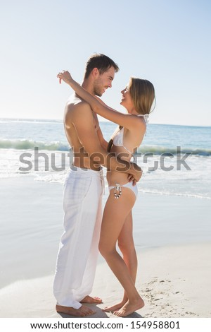 Sexy couple hugging on the beach - stock photo