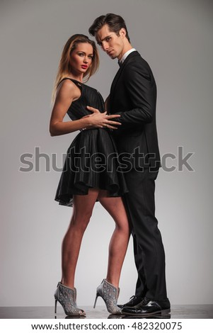 sexy couple in elegant clothes standing embraced and looking at the camera
