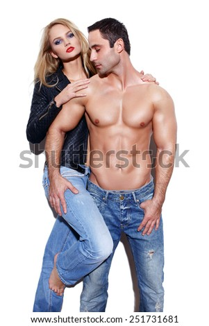 Sexy couple in jeans posing at white wall - stock photo