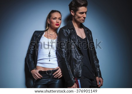 sexy couple in leather jackets pose in studio background leaning on the wall while looking away - stock photo