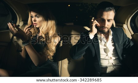 Sexy couple in the car. Young woman applying lipstick and man using cell phone in car. - stock photo