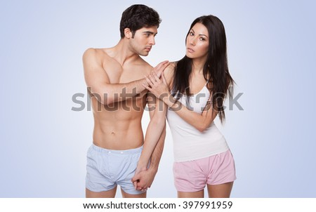 sexy couple in their underwear arguing looking at the camera