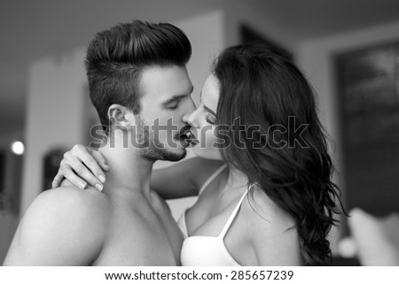 Sexy couple kissing at home, milf with young lover, black and white - stock photo
