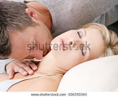 Sexy couple kissing while lounging on a white sofa at home. - stock photo