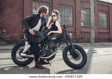 Sexy couple of bikers on the vintage custom motorcycle. Outdoor lifestyle portrait - stock photo