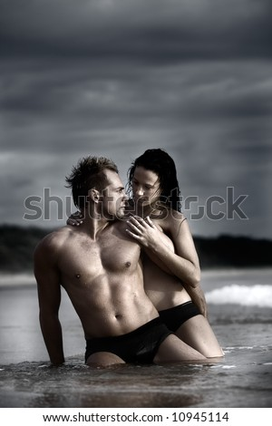 Sexy couple on beach with dark stormy clouds in background - stock photo