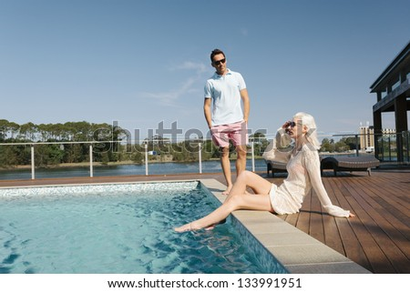 Sexy couple relaxing poolside - stock photo