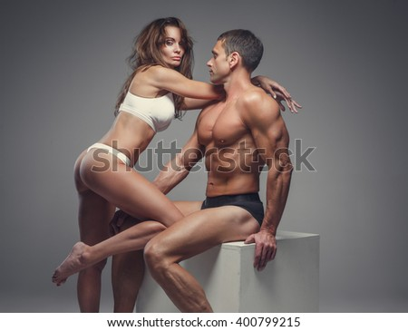 Sexy couple. Shirtless muscular middle age man and a woman in underwear posing in studio. - stock photo