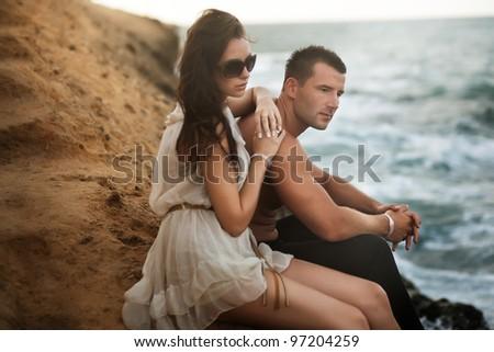 Sexy couple sitting on a rokcks - stock photo