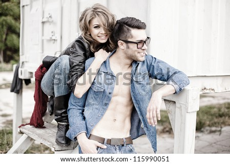 sexy couple wearing jeans and boots smiling natural - retro processed image - stock photo