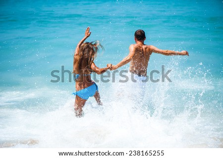 sexy couples playing in sea - stock photo