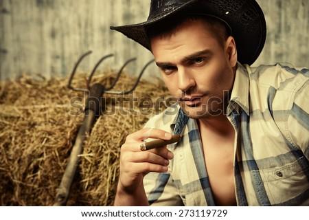 Sexy cowboy smoking a cigar. Western style. Jeans denim fashion. - stock photo