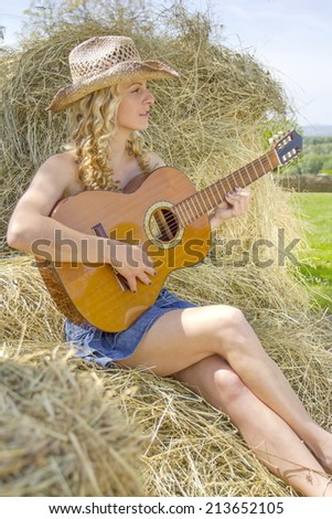 Sexy cowgirl playing on guitar, sitting on hay. - stock photo