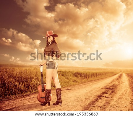 sexy cowgirl with guitar at rural sunset road - stock photo