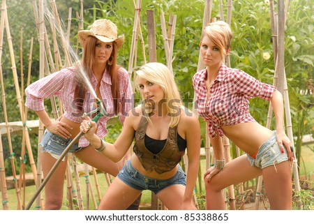 Sexy Cowgirls having fun with a water hose
