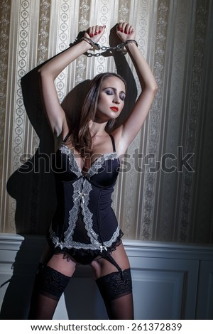 Sexy cuffed woman at vintage wall, bdsm - stock photo