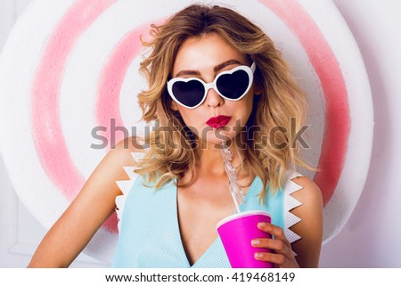 Sexy cute curly blonde  girl in sunglasses with beautiful skin and lips, posing in studio, drinking fruit juice or cocktail. Wearing vintage heart sunglasses, stylish blue leather top. - stock photo