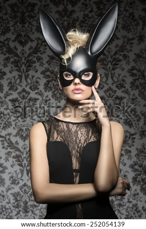 Sexy, dark, carnival, woman in black rabbit mask and black dress with nice hairstyle and dark make up.