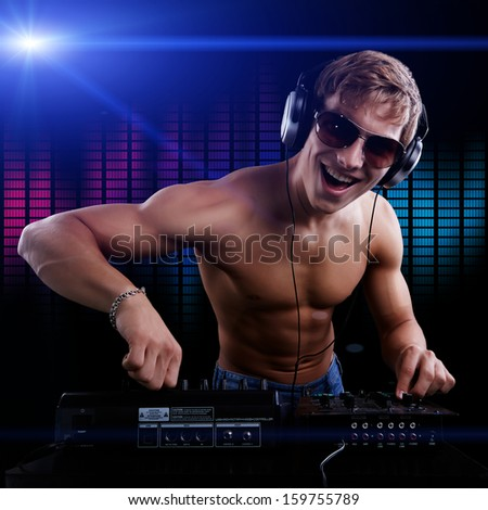 Sexy DJ macho is playing disco music in headphones and sunglasses - stock photo