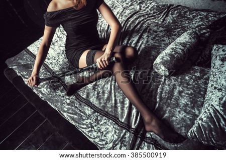 Sexy dominant girl sitting on the bed and was ready to punish his slave. In her whip hand. Top view . BDSM - stock photo