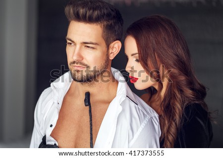 Sexy dominatrix playing with macho lover indoor - stock photo