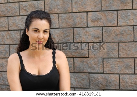 Sexy dressed mature woman on textured wall - stock photo