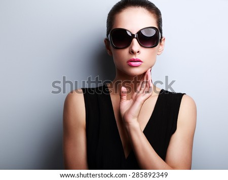 Sexy fashion female model in trendy sun glasses posing on blue background. Closeup portrait