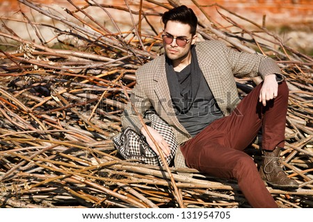 sexy fashion man model dressed elegant holding a bag posing outdoor - stock photo