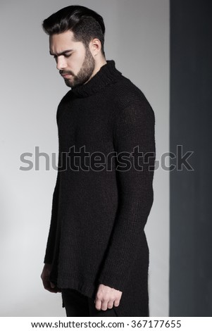 sexy fashion man model in black sweater, jeans and boots posing dramatic - stock photo