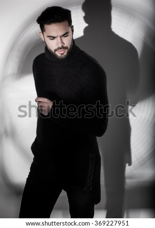 sexy fashion man model in black sweater, jeans and boots posing dramatic