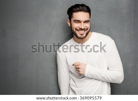 sexy fashion man model in white sweater, jeans and boots smiling against wall
