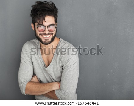 sexy fashion man with beard dressed casual smiling against wall - stock photo