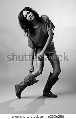 Sexy fashion model bends down to hold her boot