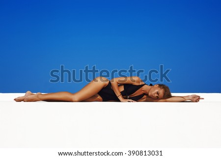 Sexy fashion model in swimwwear with skinny body against blue sky on background - stock photo