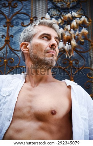 Sexy fashion portrait hot male model in stylish jeans and shirt with muscular body posing. And Dream Catcher. - stock photo