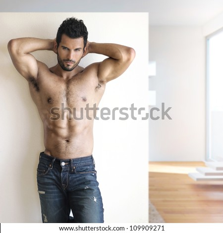 Sexy fashion portrait of a hot male model in stylish jeans with muscular body posing in modern setting - stock photo