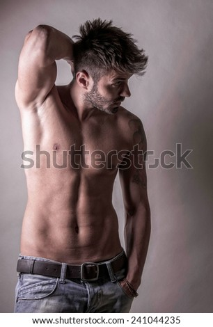 Sexy fashion portrait of a hot male model with muscular body posing in studio. - stock photo