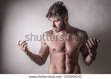 Sexy fashion portrait of a hot male model with muscular body posing in studio.