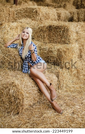 Sexy fashion woman in cow girl country style on hay stack. Beauty romantic girl outdoors against hay stack. Photo of sexy blonde in a field with haystacks - stock photo
