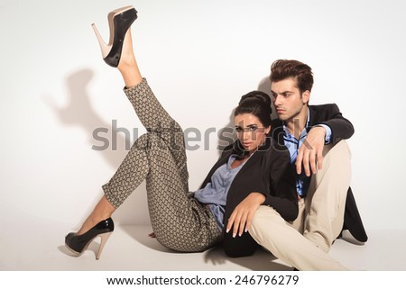 Sexy fashion woman leaning on her lover and holding one leg up while he is looking away from ther camera. Both are sitting on ther floor. - stock photo