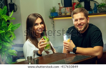 Sexy fashionable couple drinks cocktails in the bar and smiling on camera. horizontal photo of couple in love