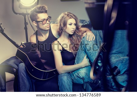 sexy fashionable couple wearing jeans posing dramatic - retro processed image - stock photo
