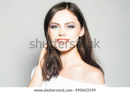 sexy fashionable girl or woman with makeup on pretty smiling face and long brunette hair in white dress with bare shoulder in studio on grey background