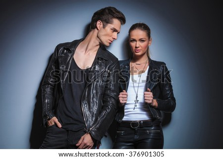 sexy fashionable man in black looking at his woman while she is posing for the camera arranging her jacket in studio background - stock photo